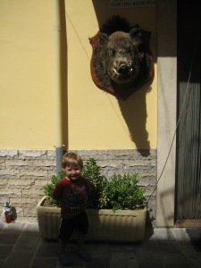 "My son with a ""cinghiale"" (wild boar) outside our favorite butcher shop in Caramanico Terme (Abruzzo)"