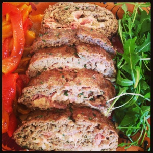 Polpettone from Naples stuffed and rolled with ham and cheese and served with roasted peppers and baby arugula